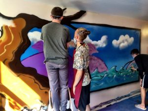 young people painting wall art